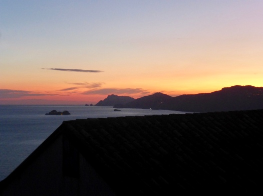 The sun sets over Capri in the distant left